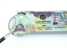 3D framförda Förenade Arabemiraten pengar med förstoringsapparaten utforskar valuta som isoleras på vit bakgrund Royaltyfria Foton