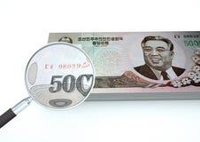 3D framförda nordkoreanska pengar med förstoringsapparaten utforskar valuta som isoleras på vit bakgrund Royaltyfri Foto