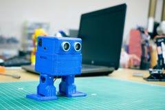 3D gedrukte Grappige blauwe robot op de achtergrond van apparaten en laptop Robotmodel op automatische driedimensionele 3d wordt  stock foto's