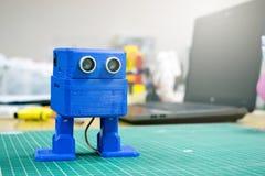 3D gedrukte Grappige blauwe robot op de achtergrond van apparaten en laptop Robotmodel op automatische driedimensionele 3d wordt  stock foto