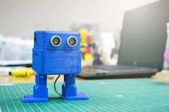 3D gedrukte Grappige dansende blauwe robot op de achtergrond van apparaten en laptop Robotmodel op automatische driedimensionele  stock afbeeldingen