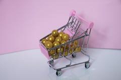 3D geproduceerd beeld Het hoogtepunt van het supermarktkarretje van gouden ballen op roze achtergrond De foto van het consumentis Stock Afbeelding