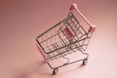 3D geproduceerd beeld Leeg Supermarktkarretje op roze achtergrond De foto van het consumentismeconcept Stock Afbeelding