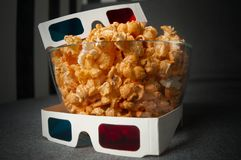 3D glasses and cheesy popcorn lie in a glass plate on a gray bed royalty free stock image