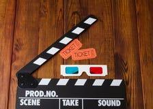 3D-glasses, filmbiljetter och filmclapperen är mot mörkt trä Royaltyfri Bild