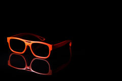 3D glasses. Isolated pair of cinema 3d plastic glasses reflected on black glass to left of frame with room for copy stock images