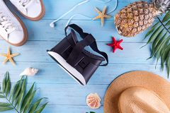 3D glasses with palm leaf, shoes, hat and pineapple on a blue wooden background. Concept of traveling in virtual reality. Flat lay stock images