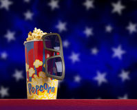 3d glasses and popcorn on armchair cinema. 3d glasses and popcorn on red armchair cinema. Blockbuster concept Royalty Free Stock Images