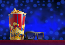 3d glasses and popcorn on armchair cinema. 3d glasses and popcorn on red armchair cinema. Blockbuster concept Stock Images