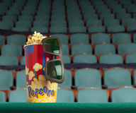 3d glasses and popcorn on green armchair cinema. Blockbuster concept Royalty Free Stock Photo