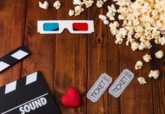 3D-glasses, popcorn, red heart, movie tickets and movie clapper. Against the dark wood Royalty Free Stock Image