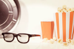 3D glasses, Popcorn and a reel, concept Cinema and movie theater Stock Photo
