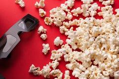 3D glazen en popcorn op rode achtergrond Stock Fotografie