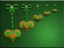 3-D glitter hearts hanging on bows w/ green background Royalty Free Stock Photos