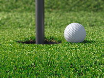 3d Golf ball by hole Stock Photo