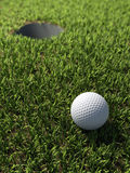 3d Golf ball by hole Royalty Free Stock Photos