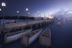 3d het teruggeven houten pijler dichtbij overzees met lamppost en boot in schemeringscène Stock Afbeeldingen