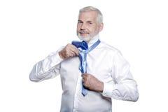 Aîné d'homme obtenant habillé attachant la cravate de windsor Images stock