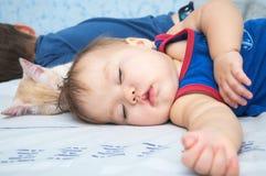 D3ia el dormir del bebé con el hermano y el gato Fotografía de archivo