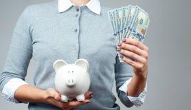 3d illustratie op witte achtergrond Het spaarvarken van de vrouwenholding en bos van geldbankbiljetten Stock Foto