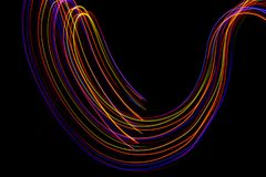 3d illustration. Abstract lines of light painting of reddish colors on black background. Abstract three-dimensional patterns royalty free stock photos