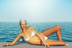 3d illustration of beautiful woman sunbathing on beach Royalty Free Stock Image