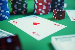 3D illustration casino game. Chips, playing cards for poker. Poker chips, red dice and money on green table. Online Stock Photos