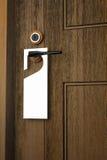 3D: Illustration des Weißbuchschildes, das an einem Griff des Holztürerholungsortes oder -hotels hängt Lizenzfreies Stockfoto
