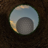 3D illustration of a golf ball going into a hole. Stock Image