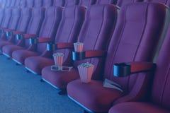 3D illustration med exponeringsglas 3d, popcorn, kopp med en drink Biobegrepp med blått ljus Röda stolar i bion vektor illustrationer