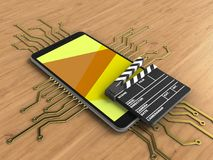 3d cinema clap. 3d illustration of mobile phone over wooden background with electronic circuit and cinema clap Royalty Free Stock Photo