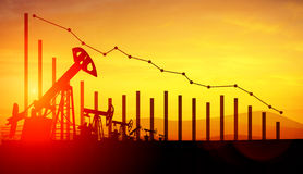 3d illustration of oil pump jacks on sunset sky background with financial analytics. Concept of falling oil prices Royalty Free Stock Image