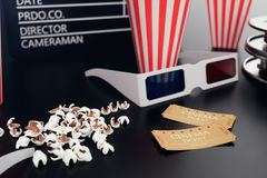 3D illustration with popcorn, cinema reel, clapperboard and two tickets at black backgorund with blue light. Concept. Cinema and theater vector illustration