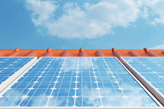 3D illustration solar panels on a red roof reflecting the cloudless blue sky. Energy and electricity. Alternative energy. Eco or green generators. Power Royalty Free Stock Image