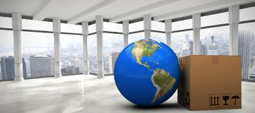 Composite image of 3d image of planet earth by cardboard box. 3D image of planet Earth by cardboard box against modern room overlooking city Stock Image