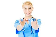 D'infirmière de Holding Blocks Spelling santé au-dessus du fond blanc Photos stock
