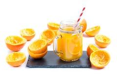 D'isolement dans le jus d'orange sur le verre sur l'ardoise Photos stock