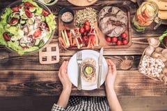 D?jeuner ? la table avec la nourriture diff?rente, les mains des femmes avec un plat images libres de droits