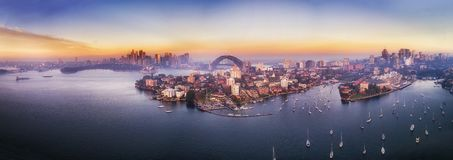 D Kirrib 2 CBD Marina pink rise pan. Elevated aerial panorama over local bay with marina and yachts on Sydney harbour in view of major city CBD landmarks at stock photo
