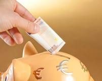 Dé la inserción de un billete de banco en una hucha, concepto del euro cincuenta para el negocio y ahorre el dinero Imagen de archivo libre de regalías