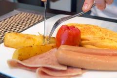 Dé la patata del corte en plato del desayuno con la tortilla, salchichas, jamón, tomate, patatas fritas en la placa blanca Imagen de archivo libre de regalías