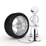 The 3D little man pumps up a wheel. Stock Photo