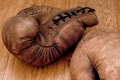 3d lokalisiert auf wei?em Hintergrund Retro- Paare der alten Weinlese der ledernen abgenutzten Handschuhe sind auf der h?lzernen  stockbilder