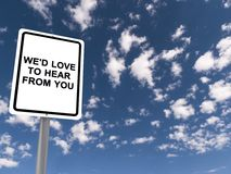 We'd love to hear from you. Text 'we'd love to hear from you' in black uppercase letters on white highway style sign board, background of blue sky and cloud Stock Images