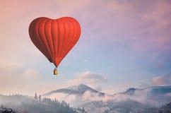D luchtballon in de vorm van een hart die in ochtendbergen vliegen royalty-vrije stock foto's