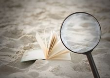 3D Magnifying glass over book in sand. Digital composite of 3D Magnifying glass over book in sand Stock Photos