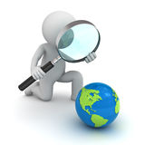 3d man holding magnifying glass and looking at blue globe map Royalty Free Stock Photography