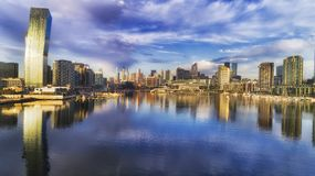 D Me Docklands Low Bend. Still Yarra river bay water reflects modern urban architecture of Melbourne Dockalds suburb with bended apartment tower and high-rise Royalty Free Stock Photos