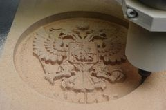 3d milling machine on a tree, cut the coat of arms of Russia in the bar. Close-up stock footage