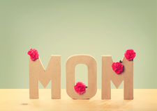 3D MOM Text with Carnation Flowers on the Table Royalty Free Stock Photos